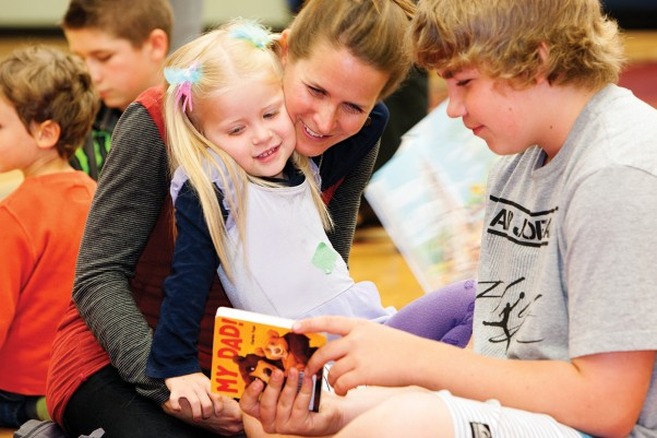 "Grade 7 Brooklyn Elementary student Kyle reads to three-year-old Aria while her mom Lana looks on, as part of the StrongStart ""Big Buddy Day,"" where older students mentor the young kids in the StrongStart program.  Photo by Boomer Jerritt"